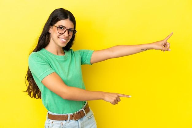Молодая кавказская женщина изолирована на желтом фоне, указывая пальцем в сторону и представляет продукт