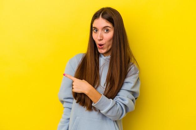 側面を指している黄色の背景に分離された若い白人女性