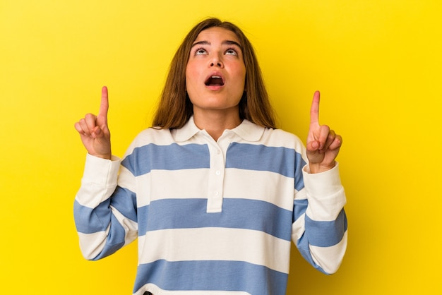 열린 된 입으로 거꾸로 가리키는 노란색 배경에 고립 된 젊은 백인 여자.