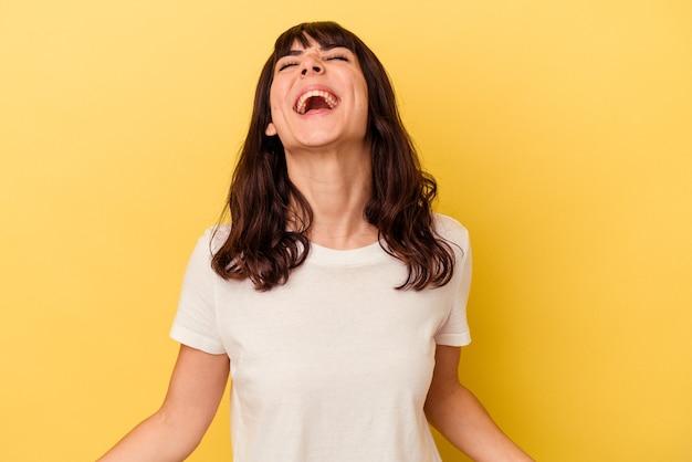 노란색 배경에 고립 된 젊은 백인 여자 편안 하 고 행복 한 웃음, 목 뻗어 보여주는 이빨.