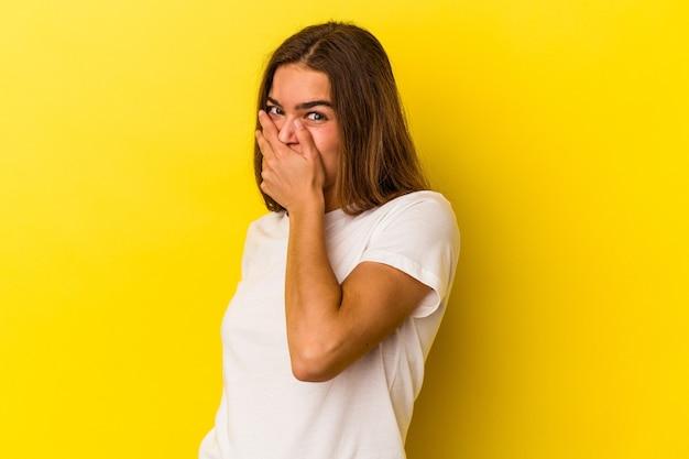 Молодая кавказская женщина, изолированные на желтом фоне, испугалась и испугалась.
