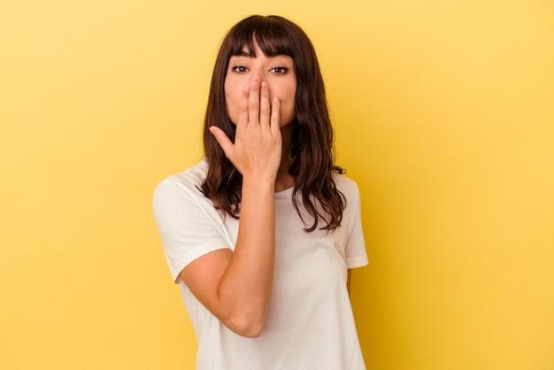 노란색 배경에 고립 된 젊은 백인 여자 충격, 손으로 입을 덮고, 새로운 것을 발견 하 고 싶어.
