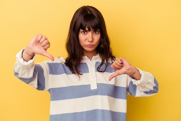 싫어하는 제스처, 엄지 손가락을 보여주는 노란색 배경에 고립 된 젊은 백인 여자. 불일치 개념.