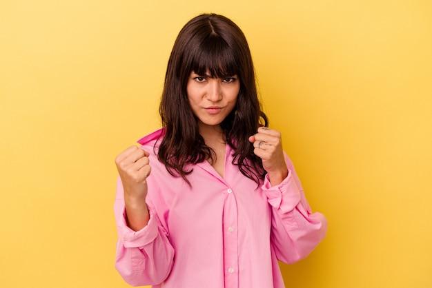 카메라, 공격적인 표정에 주먹을 보여주는 노란색 배경에 고립 된 젊은 백인 여자.