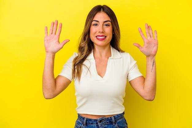 手で 10 番を示す黄色の背景に分離された若い白人女性。