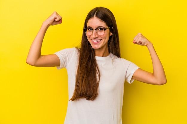 女性の力の象徴である腕で強さのジェスチャーを示す黄色の背景に分離された若い白人女性