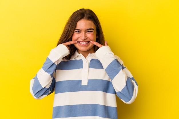 입에 손가락을 가리키는 노란색 배경 미소에 고립 된 젊은 백인 여자.