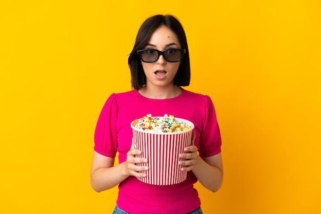 노란색 배경에 고립 된 젊은 백인 여자 3d 안경에 놀란 팝콘의 큰 양동이 들고