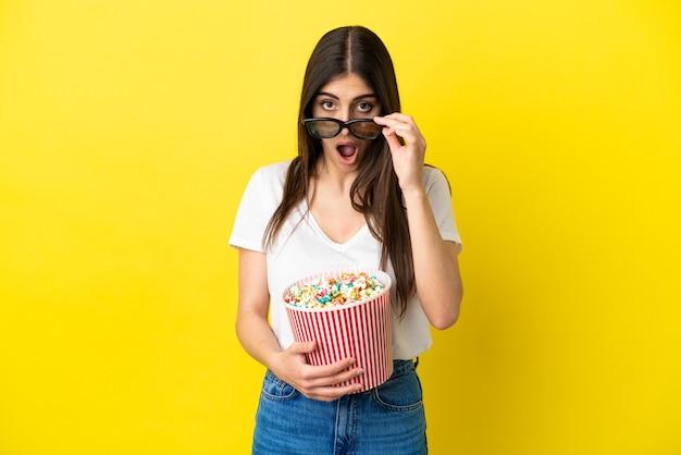 노란색 배경에 격리된 젊은 백인 여성은 3d 안경에 놀라고 큰 팝콘 양동이를 들고 있다