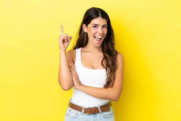 Молодая кавказская женщина изолирована на желтом фоне, думая об идее, указывая пальцем вверх