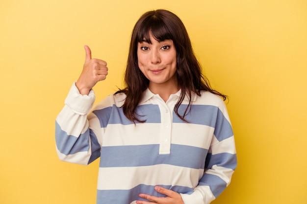 黄色い背景に隔離された若い白人女性がお腹に触れ、優しく微笑み、食事と満足のコンセプトを表現する