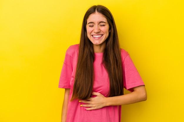 黄色の背景に分離された若い白人女性はおなかに触れ、優しく微笑んで、食事と満足の概念。