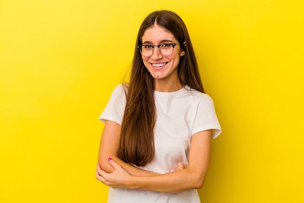 自信を持って、決意を持って腕を組んで、黄色の背景に孤立した若い白人女性。