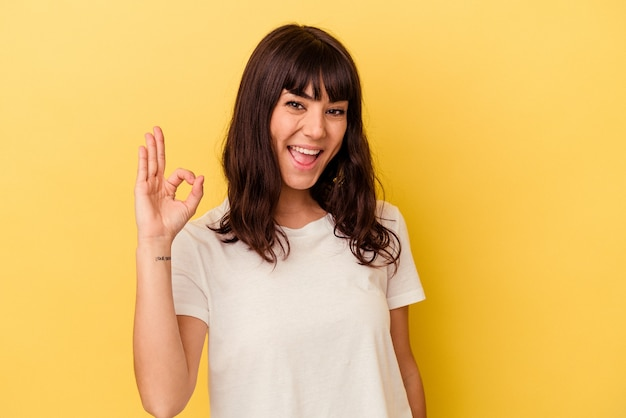 노란색 배경에 고립 된 젊은 백인 여자는 눈을 윙크 하 고 손으로 괜찮아 제스처를 보유하고있다.