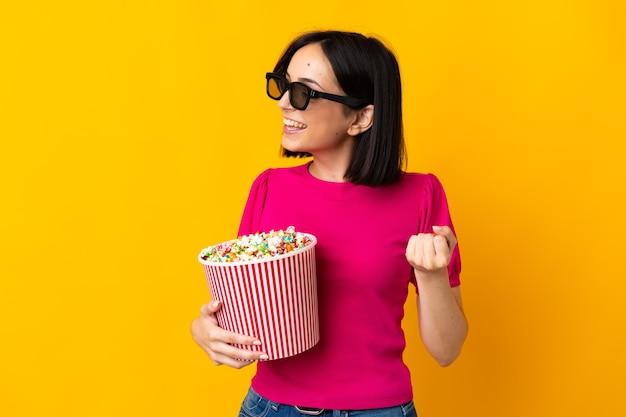 3d 안경 노란색 배경에 고립 된 측면을 보면서 팝콘의 큰 양동이를 들고 젊은 백인 여자