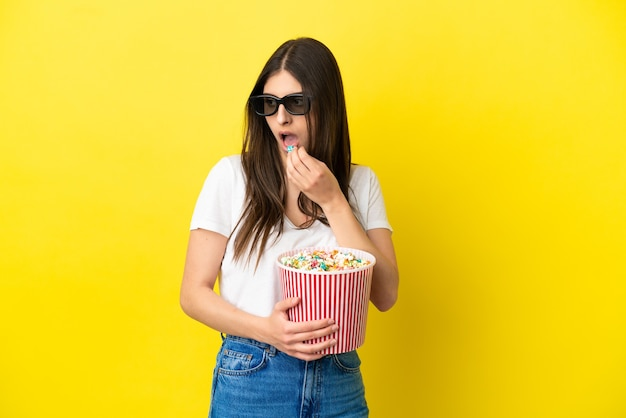 Молодая кавказская женщина изолирована на желтом фоне в 3d-очках и держит большое ведро попкорна, глядя в сторону
