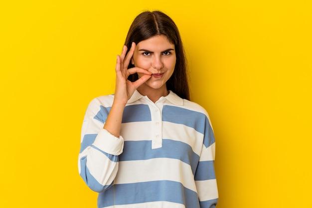 비밀을 유지하는 입술에 손가락으로 노란색 배경에 고립 된 젊은 백인 여자.