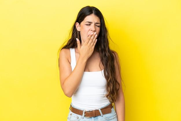 あくびと手で大きく開いた口を覆う黄色の背景に分離された若い白人女性