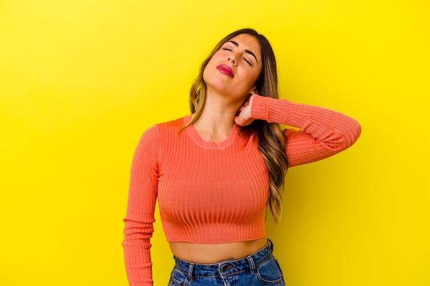 스트레스로 인해 목에 통증이 있고 마사지하고 손으로 만지는 노란색에 고립 된 젊은 백인 여자.
