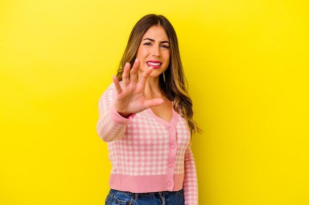 猫を模倣した爪、攻撃的なジェスチャーを示す黄色で隔離された若い白人女性。