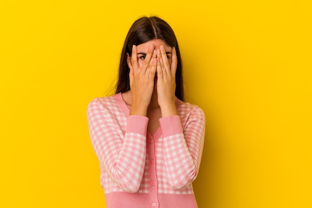 黄色い壁に隔離された若い白人女性は、恥ずかしそうに顔を覆って、指でカメラを瞬きます。