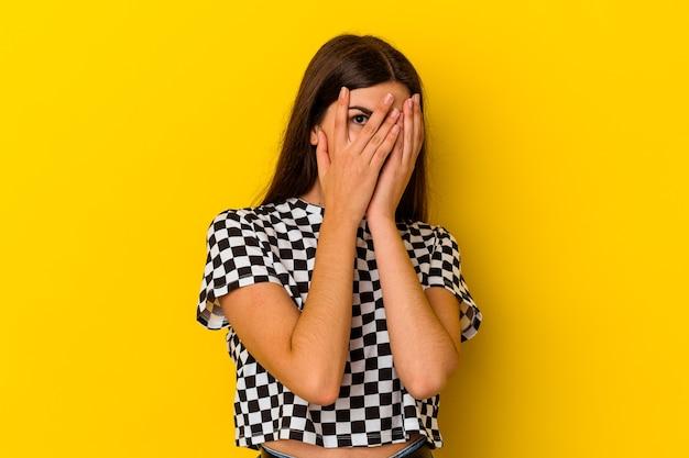 黄色い壁に隔離された若い白人女性は、おびえ、神経質な指を点滅します。