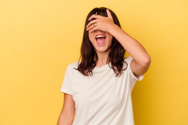 노란색 벽에 고립 된 젊은 백인 여자는 놀람을 광범위 하 게 기다리고 미소 손으로 눈을 다룹니다.