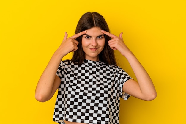 Молодая кавказская женщина, изолированная на желтой стене, сосредоточилась на задаче, держа указательные пальцы, указывая головой.