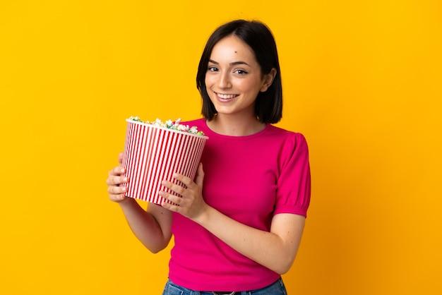 Молодая кавказская женщина изолирована на желтой стене, держа большое ведро попкорна