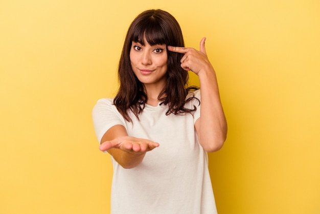 노란색 벽 잡고 손에 제품을 보여주는에 고립 된 젊은 백인 여자.
