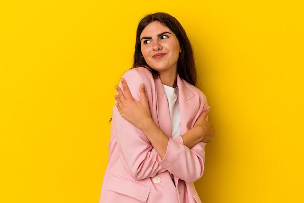 黄色の壁の抱擁に隔離され、のんきと幸せな笑顔の若い白人女性