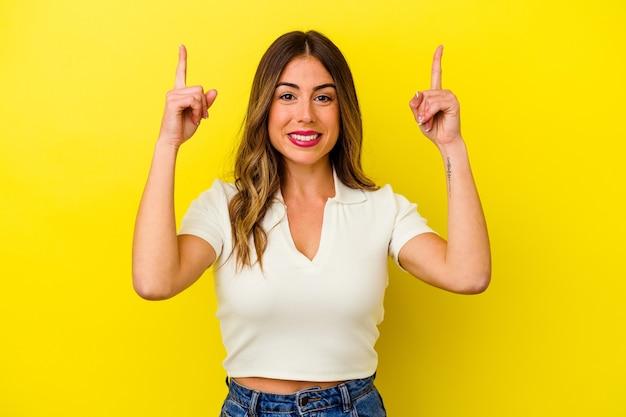노란색 벽에 고립 된 젊은 백인 여자는 빈 공간을 보여주는 두 앞 손가락으로 나타냅니다.