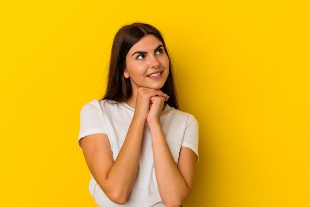 Молодая кавказская женщина, изолированная на желтой стене, держит руки под подбородком, счастливо смотрит в сторону.