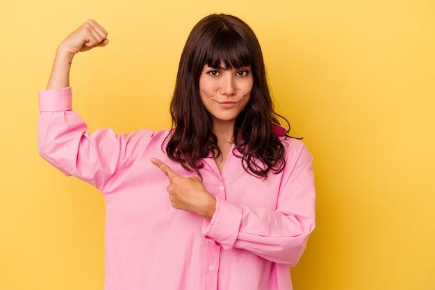 Молодая кавказская женщина изолирована на желтой стене, показывая жест силы руками, символ женской силы