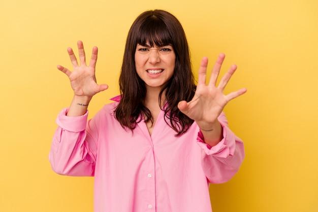 노란색 벽에 고립 된 젊은 백인 여자는 긴장된 손으로 비명 화가.