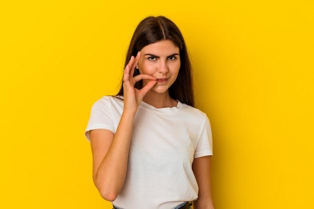 비밀을 유지하는 입술에 손가락으로 노란색 벽에 고립 된 젊은 백인 여자