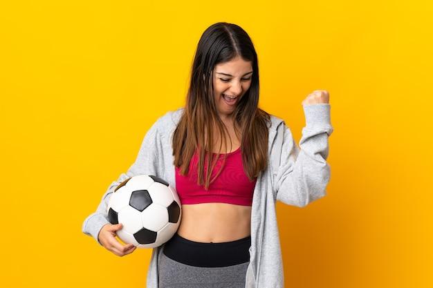 勝利を祝うサッカーボールと黄色の壁に孤立した若い白人女性