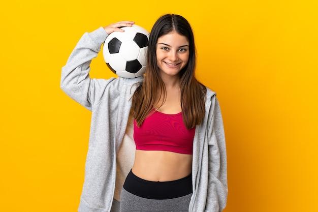 Молодая кавказская женщина изолирована на желтой стене с футбольным мячом