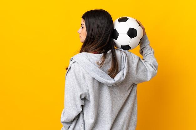 サッカーボールと黄色の壁に分離された若い白人女性