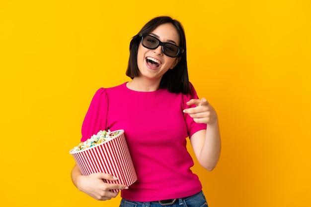 3dメガネで黄色に分離され、正面を指してポップコーンの大きなバケツを保持している若い白人女性