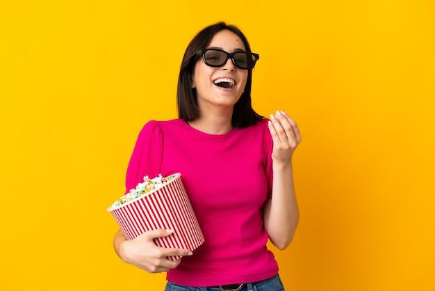 Молодая кавказская женщина изолирована на желтом в 3d-очках и держит большое ведро попкорна