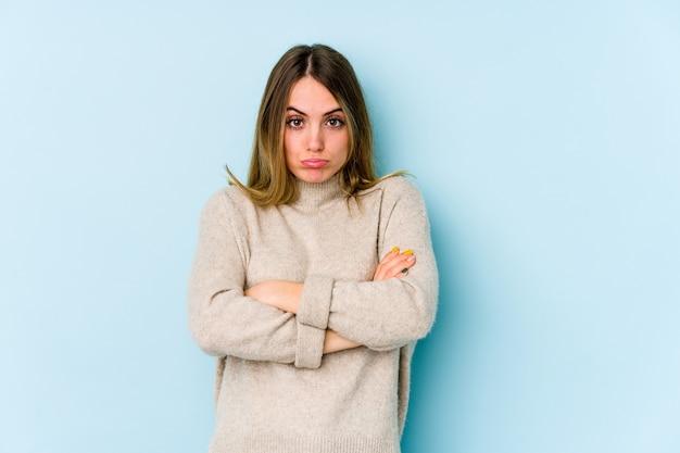 青い頬を吹く上に孤立した若い白人女性は、表現に疲れています。顔の表現のカバーセプト。