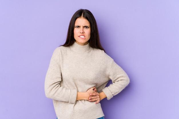Молодая кавказская женщина изолирована над фиолетовым с болью в печени, болит живот.