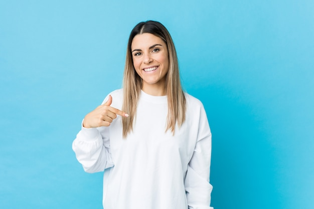 Young caucasian woman isolated person pointing by hand to a shirt copy space, proud and confident