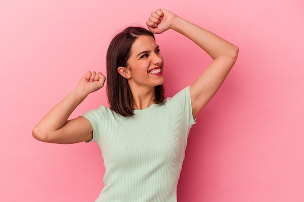Young caucasian woman isolated on pink background celebrating a special day, jumps and raise arms with energy.
