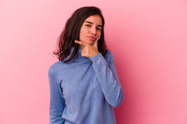 Young caucasian woman isolated on pink background contemplating, planning a strategy, thinking about the way of a business.
