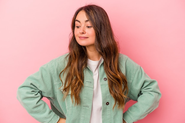 Young caucasian woman isolated on pink background dreaming of achieving goals and purposes