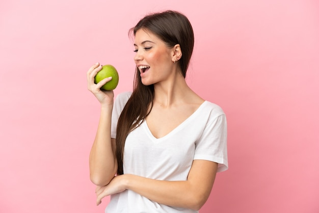 Young caucasian woman isolated on pink background eating an apple