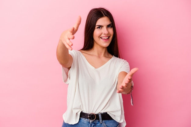 Young caucasian woman isolated on pink background feels confident giving a hug to the camera.