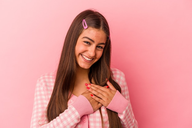 Young caucasian woman isolated on pink background has friendly expression, pressing palm to chest. love concept.